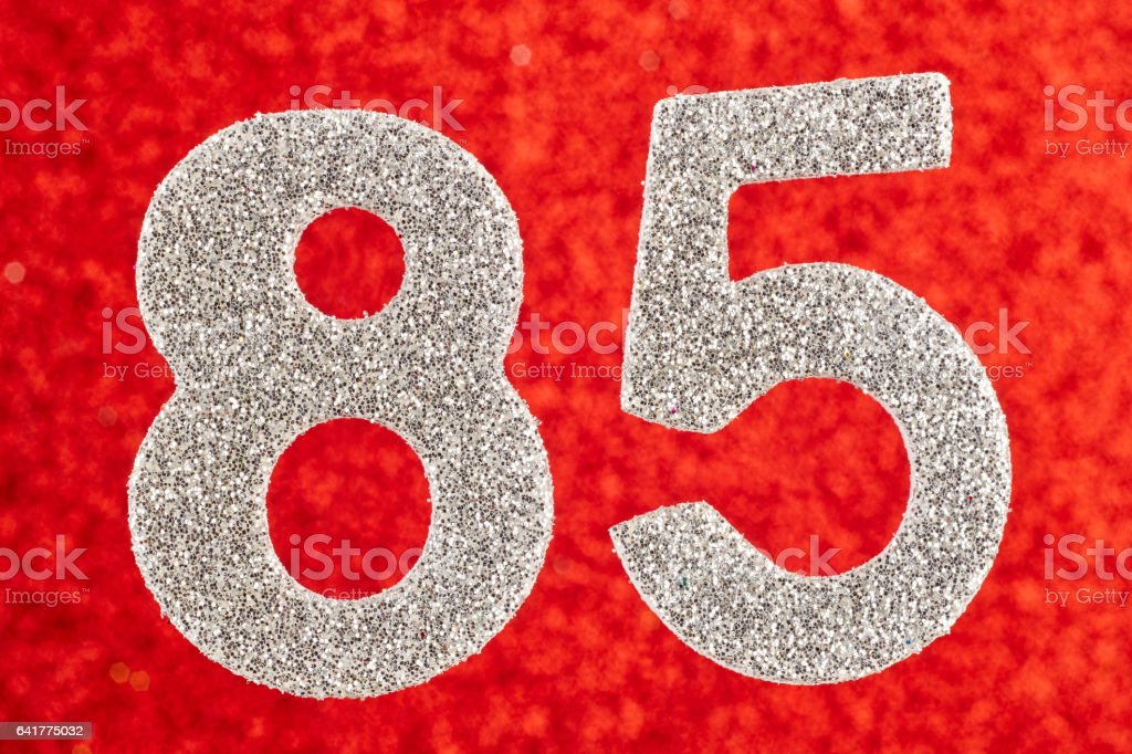 Number eighty-five silver color over a red background. Anniversary. stock photo