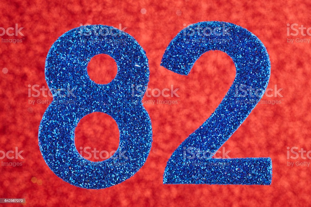Number eighty-two blue color over a red background. Anniversary. stock photo