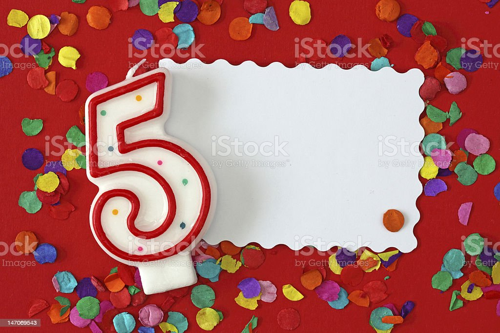 Number five birthday candle on red background with confetti stock photo
