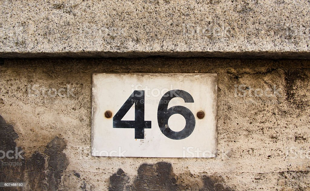 Number forty six on the grey stone wall stock photo