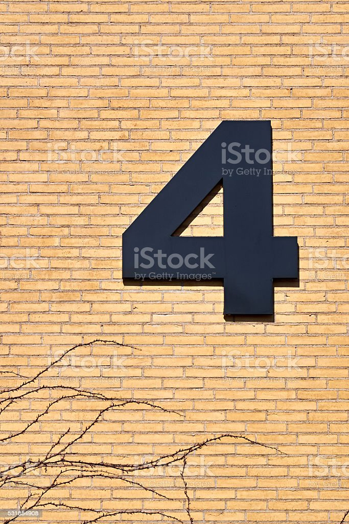 number four attached to a yellow wall stock photo