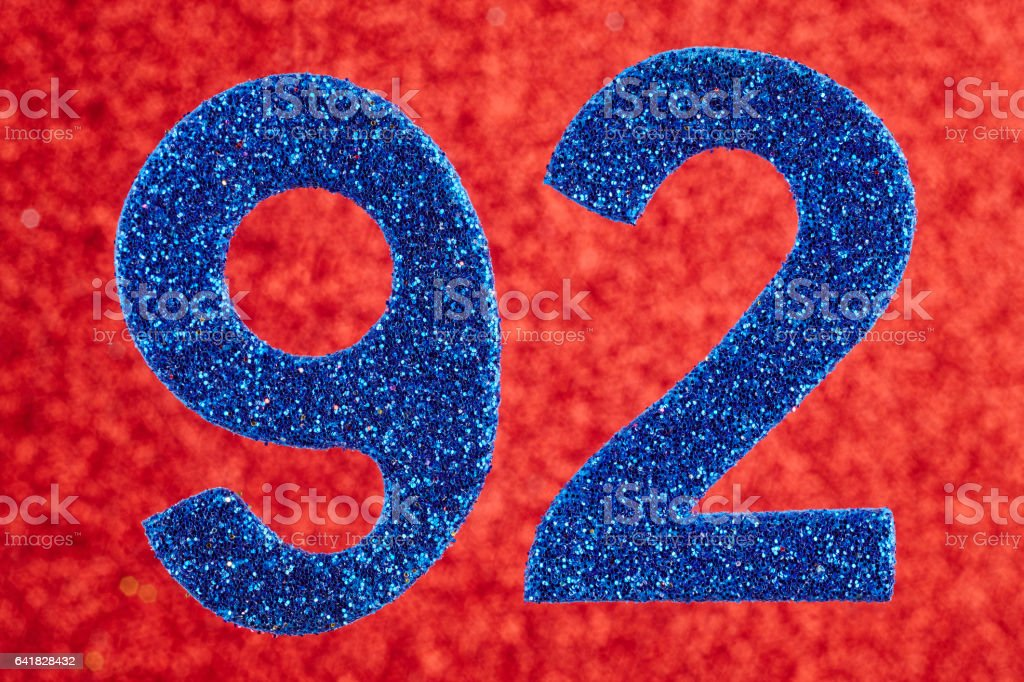 Number ninety-two blue color over a red background. Anniversary. stock photo