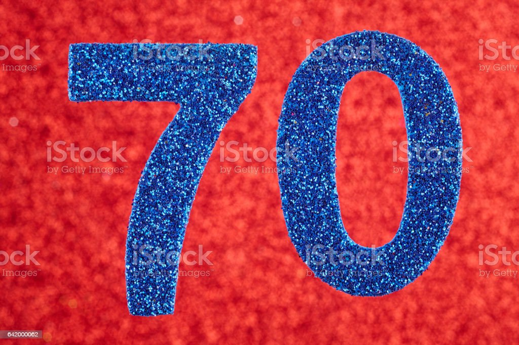 Number seventy blue color over a red background. Anniversary. stock photo