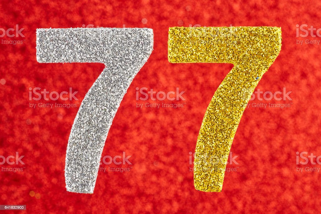 Number seventy-seven yellow silver color over a red background. Anniversary stock photo