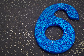 Number six blue color over a black background. Anniversary