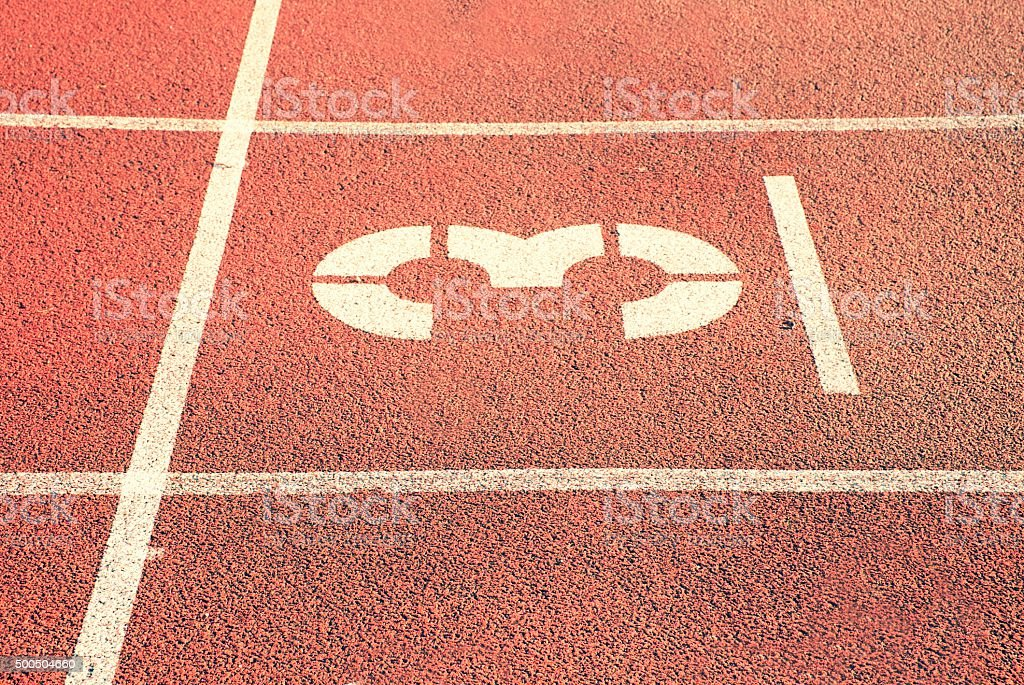 Number three. White track number on red rubber racetrack, texture of...