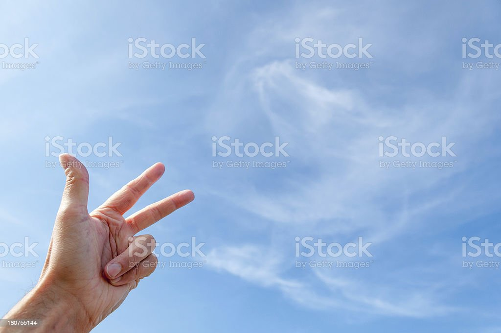 number three with a hand against blue sky, soft clouds stock photo