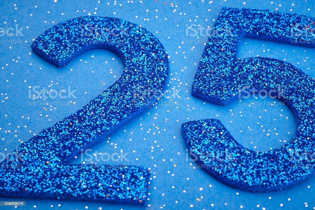 Number twentyfive blue color over a blue background. Anniversary stock photo