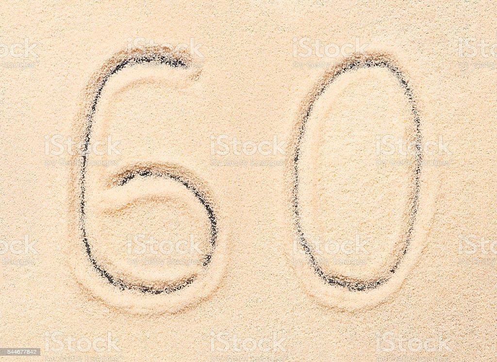 60 number written on beach sand. Summer background stock photo