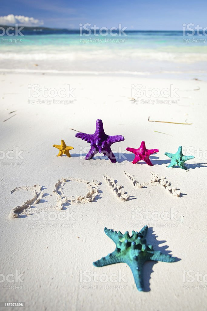 Numbers 2014 on white sandy beach royalty-free stock photo