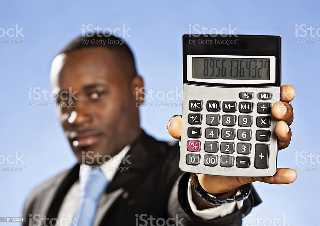 Numbers don't lie! Serious businessman holds out calculator royalty-free stock photo