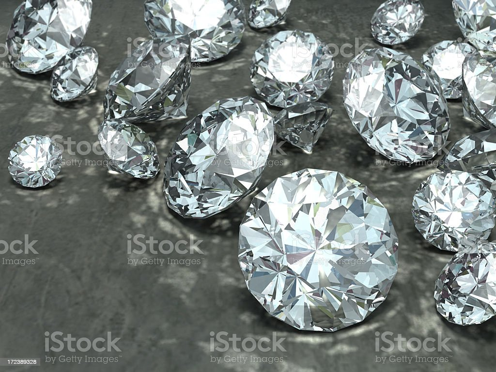 Numerous different sized diamonds laid on grey surface stock photo