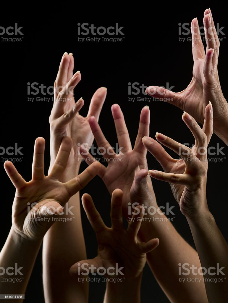 Numerous Female Hands Reaching Out from a Black Background royalty-free stock photo