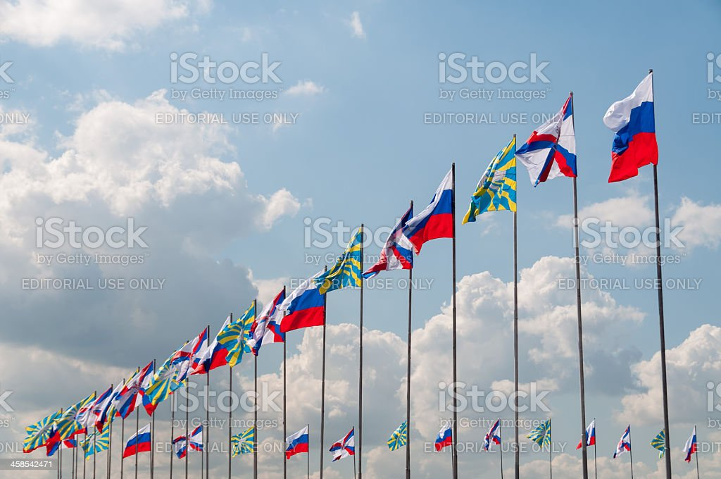Numerous flags in row against cloudy sky background royalty-free stock photo
