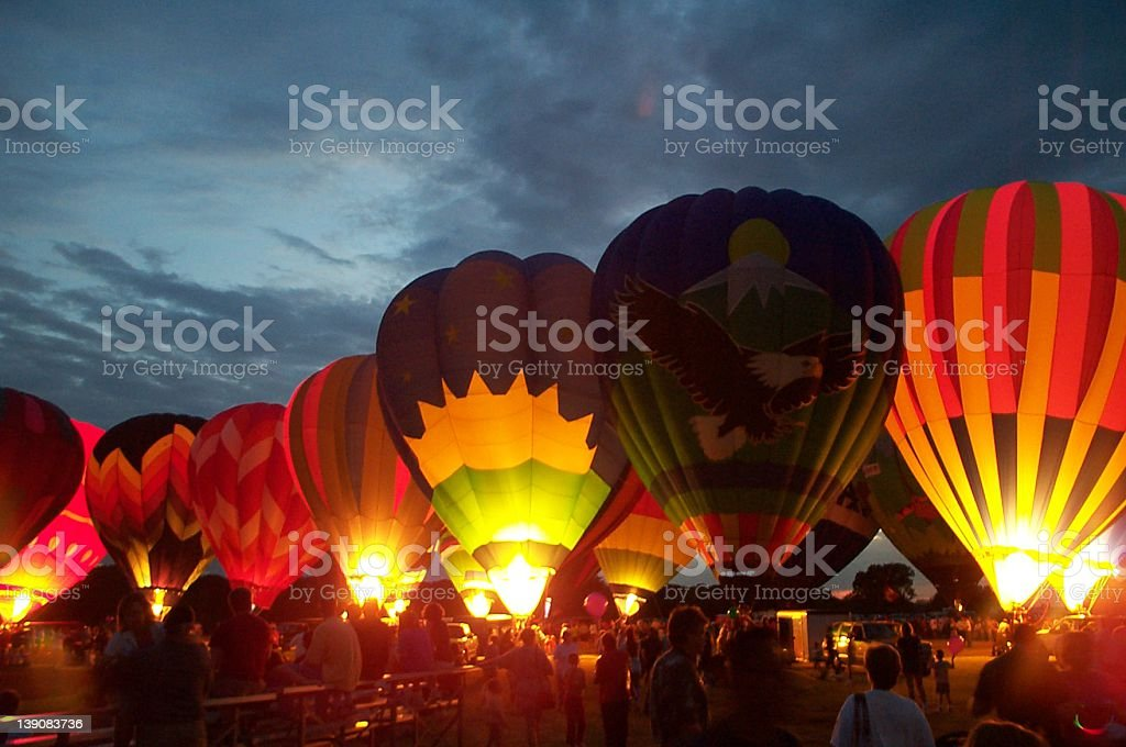 Numerous hot air balloons lined up, all aglow, at sunrise royalty-free stock photo