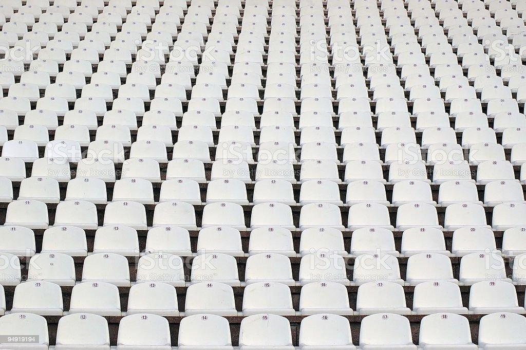 Numerous rows of white stadium seats stock photo