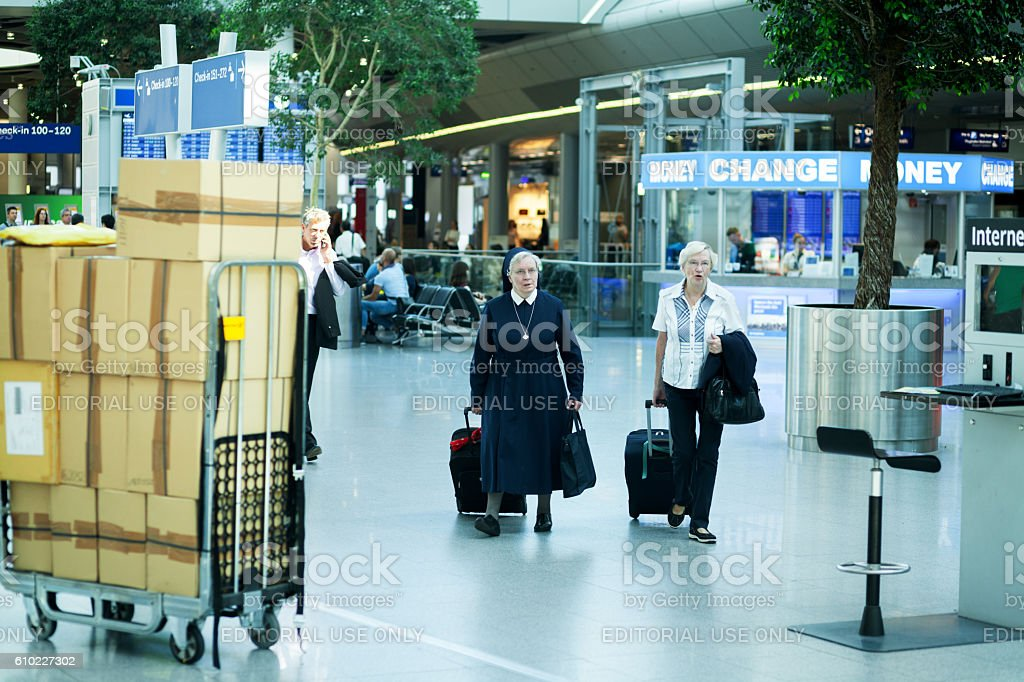 Nun and senior woman at airport stock photo