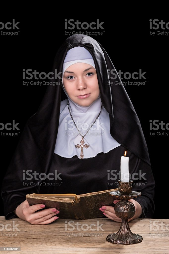 Nun at a table with book stock photo