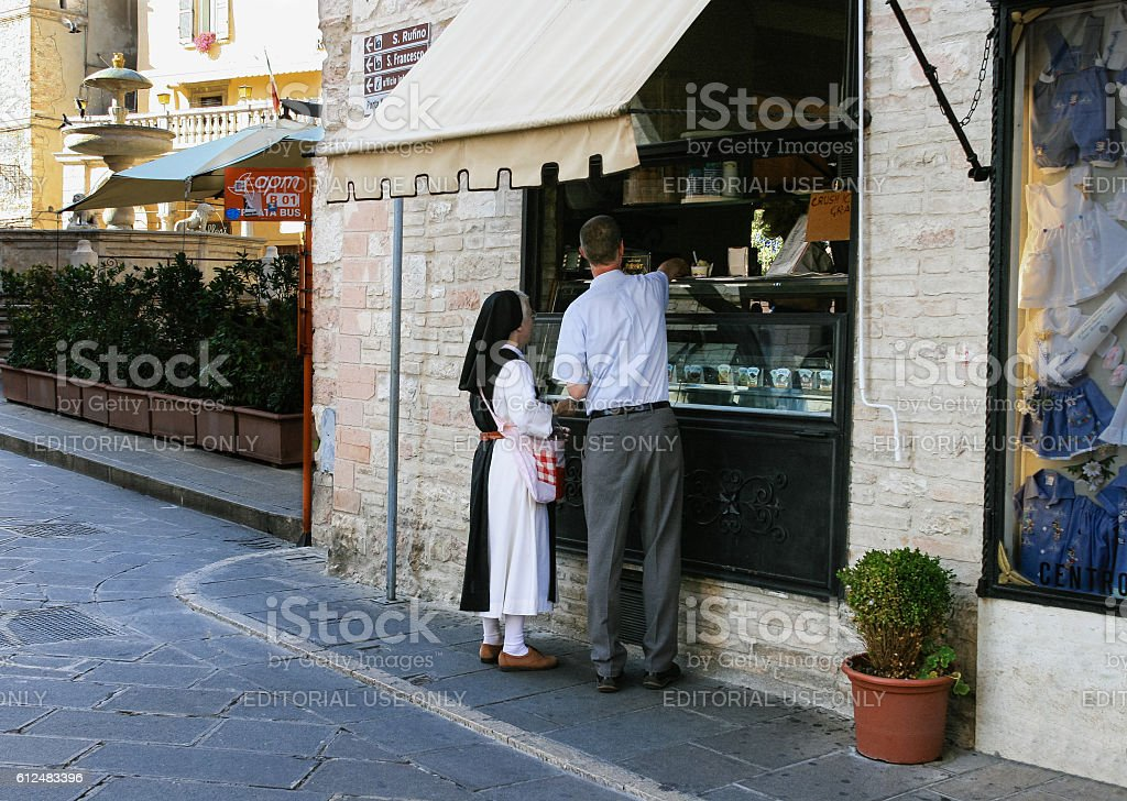Nun Bying Ice Cream on a Street of Assisi, Italy. stock photo