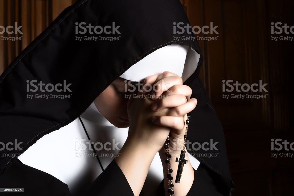 Nun folding hands holding a rosary praying stock photo