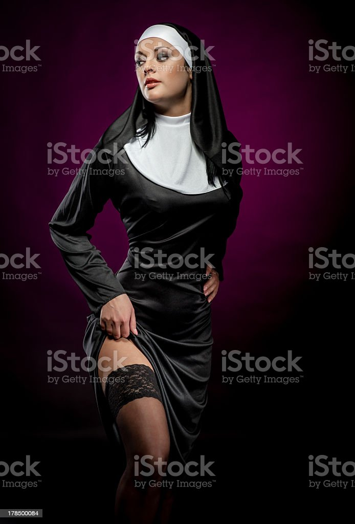 A nun hiking up her clothing on a dark background stock photo