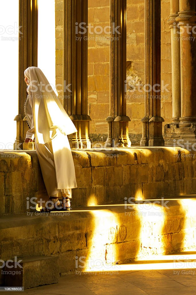 Nun in cloister archway stock photo