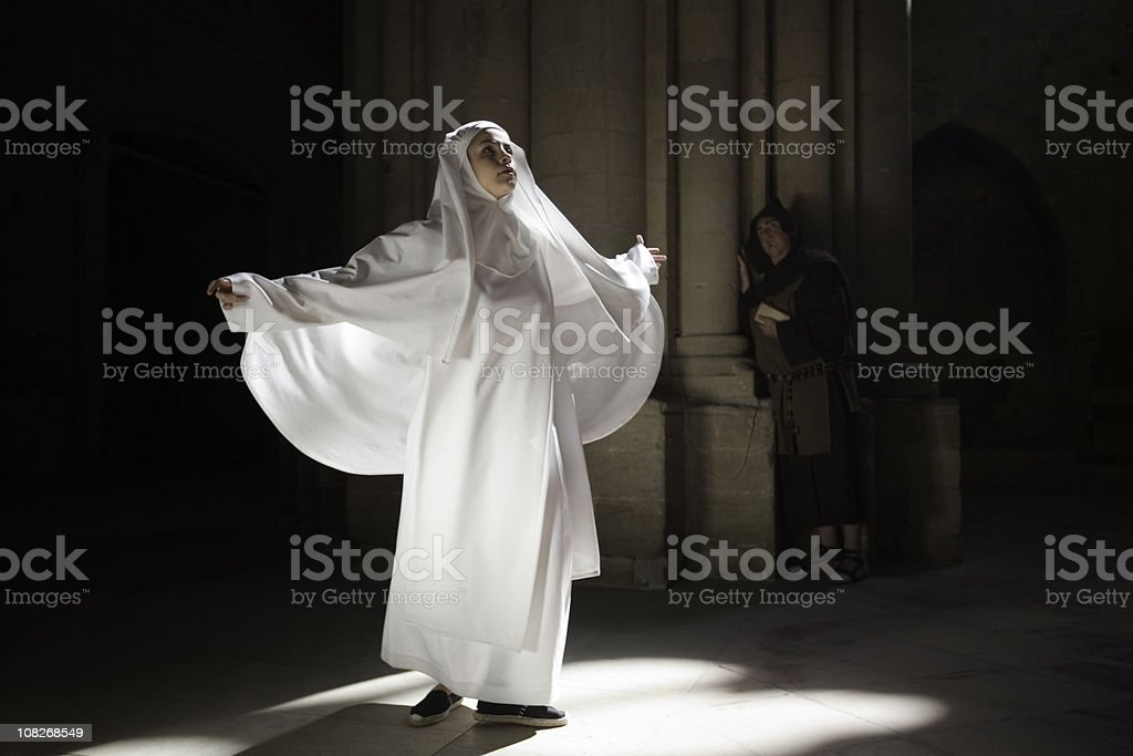Nun meditating in sunlight from cathedral window, monk watching. stock photo
