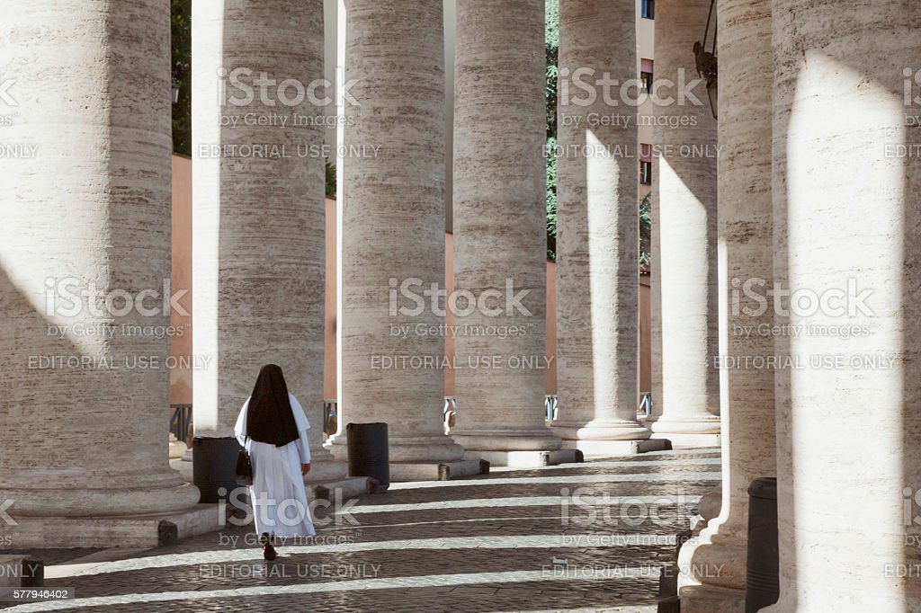 Nun walking among Bernini's Colonnade in St. Peter's Square, Vatican stock photo