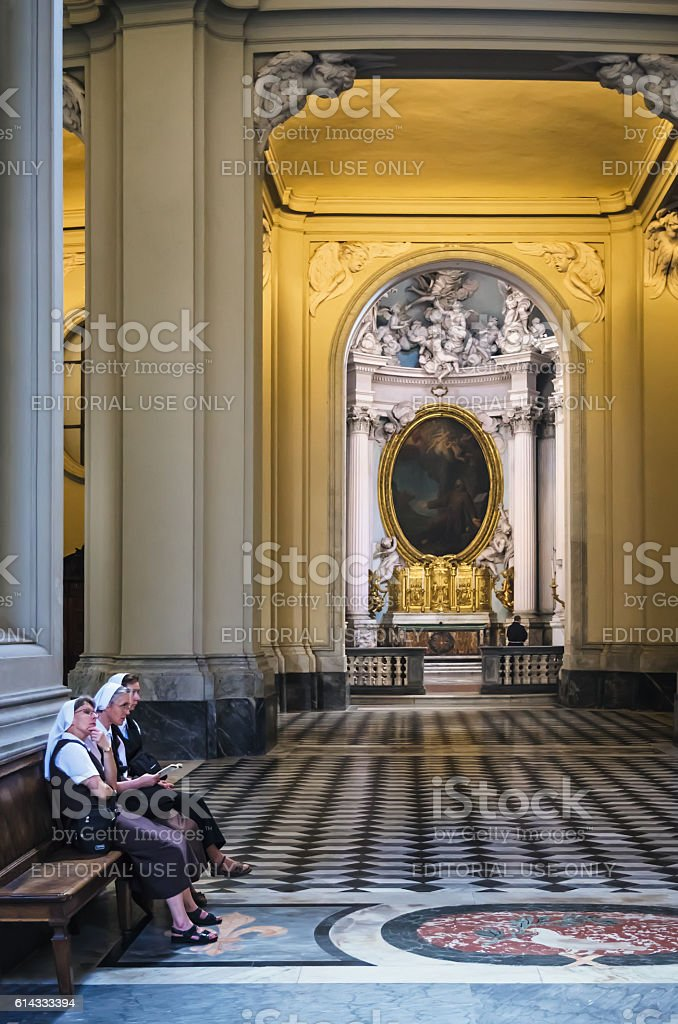 Nuns sitting inside the cathedral of Rome, Italy stock photo