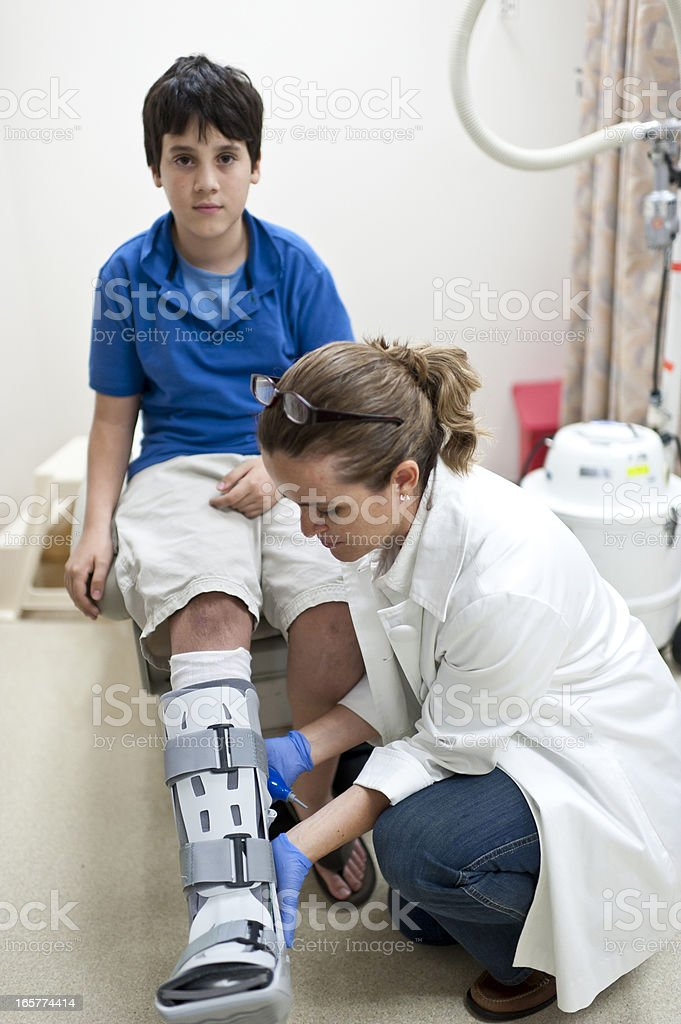Nurse adjusting orthopedic boot to a child stock photo