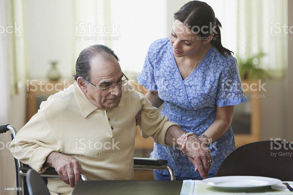 Nurse aiding an elderly man stand up from wheelchair stock photo