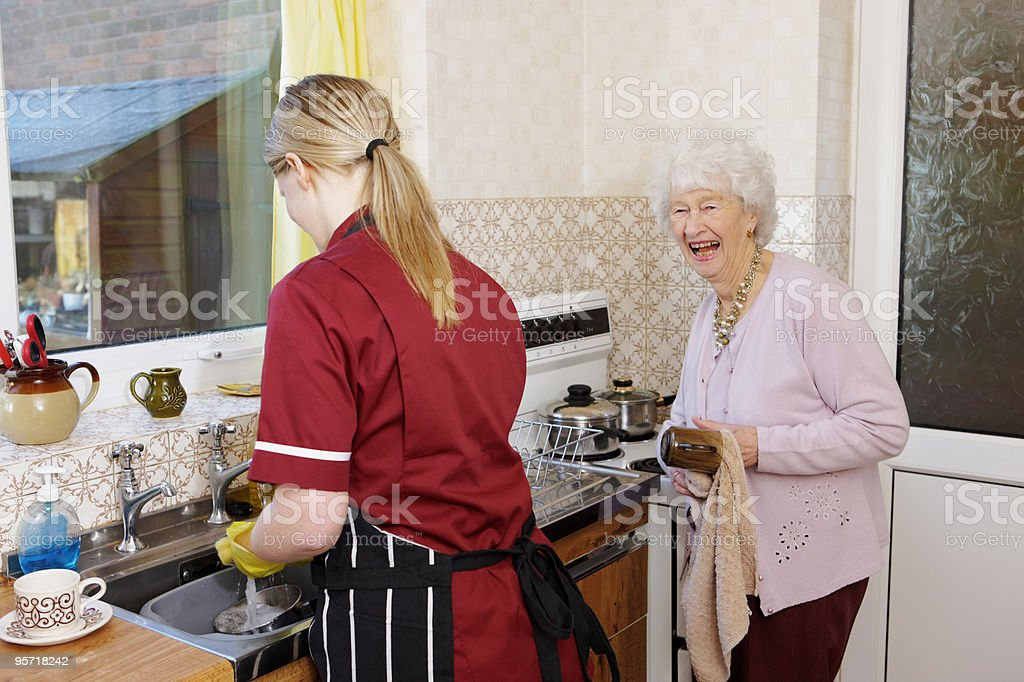Nurse and happy senior lady doing dishes in kitchen stock photo
