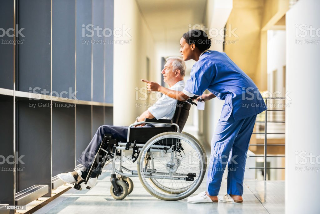 Nurse and Mature Man in Wheelchair royalty-free stock photo