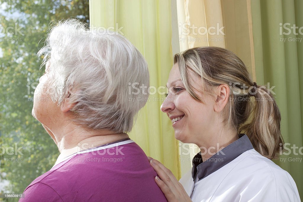 Nurse and old woman standing at the window royalty-free stock photo