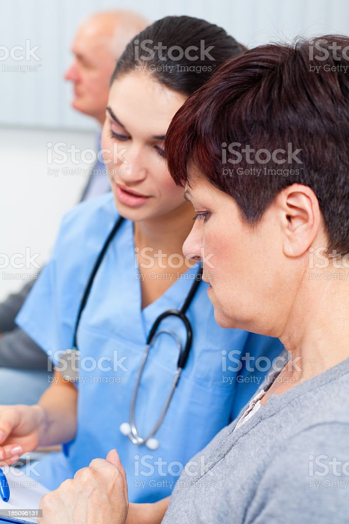 Nurse and patient examining medical records stock photo