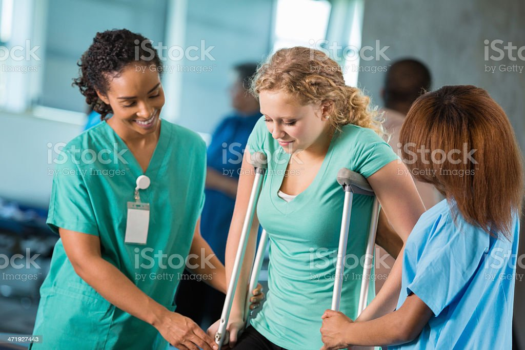 Nurse and phycial therapist assisting teen patient on crutches stock photo
