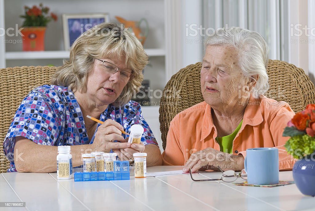 Nurse and senior citizen looking at pill bottles royalty-free stock photo