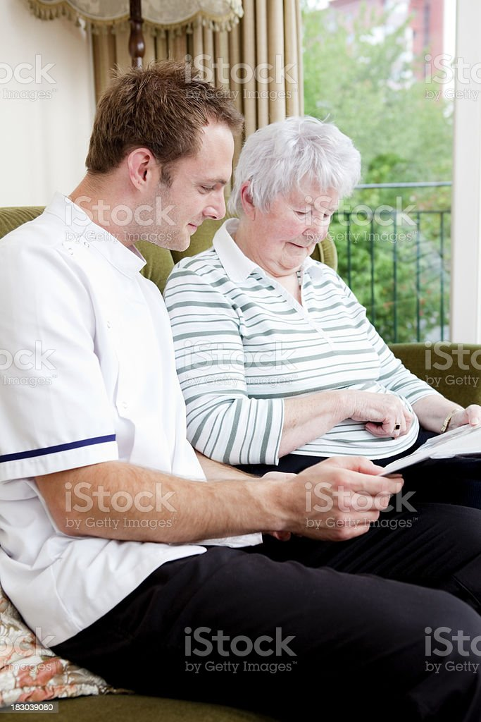 Nurse and senior lady looking through pictures in care home royalty-free stock photo