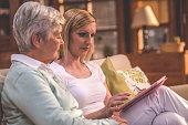 Nurse and senior woman looking into digital tablet
