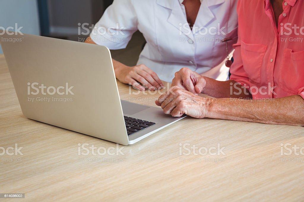 Nurse and senior woman using a laptop stock photo