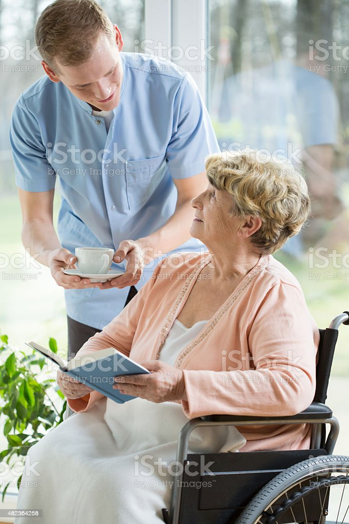 Nurse and woman on a wheelchair stock photo
