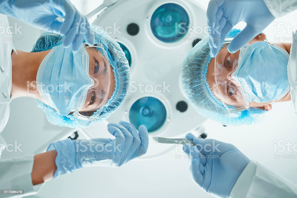Nurse assistant passes a scalpel to surgeon stock photo