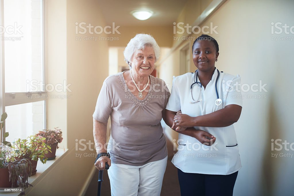Nurse assisting a senior patient to walk stock photo