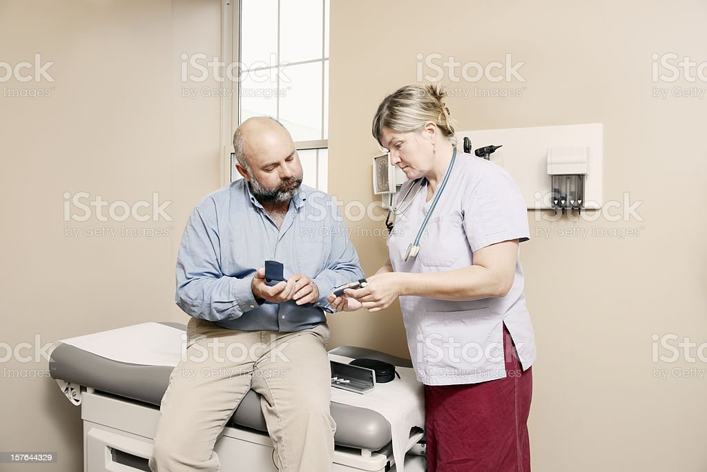 Nurse assisting diabetic patient with equipment royalty-free stock photo