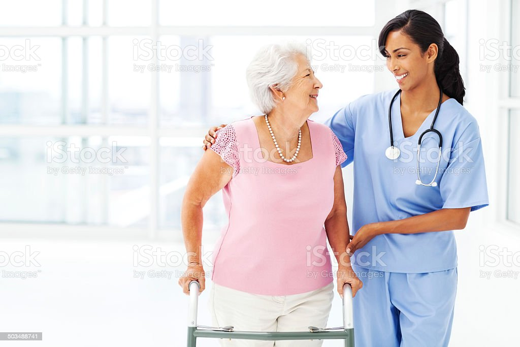 Nurse Assisting Elderly Woman With Walker While Looking At Her stock photo