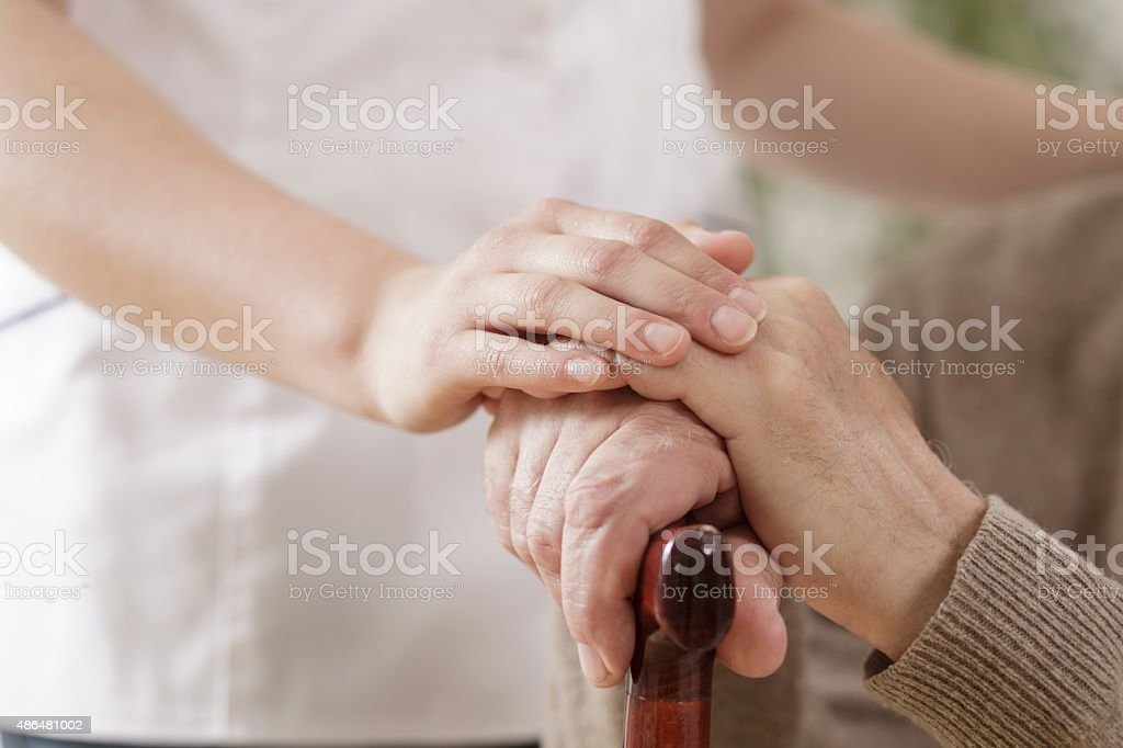 Nurse assisting ill elder man stock photo