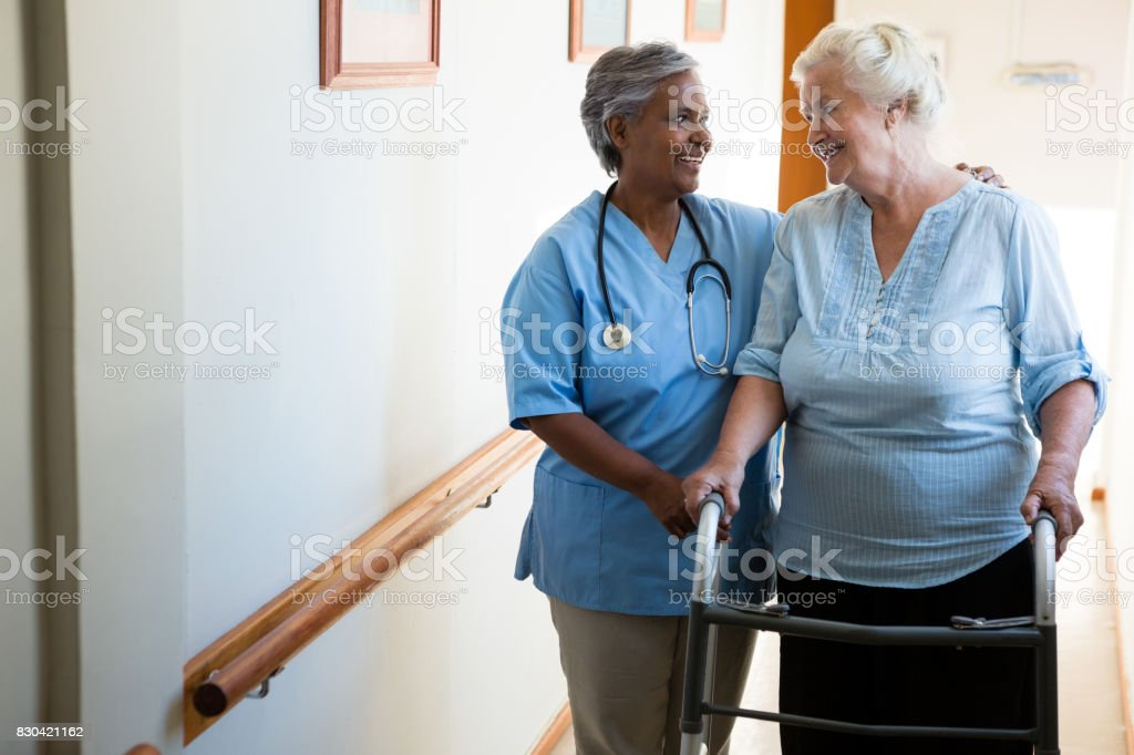 Nurse assisting senior patient in walking with walker at retirement...