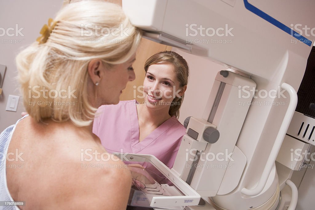 Nurse Assisting Patient Undergoing Mammogram stock photo