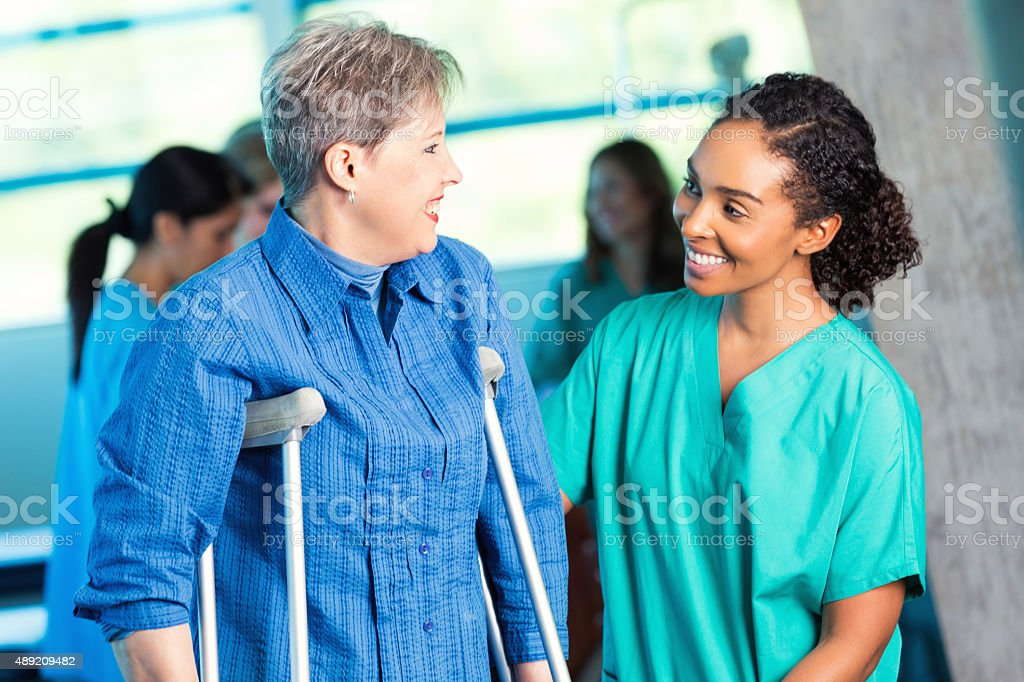 Nurse assisting senior patient during physical therapy appointment stock photo