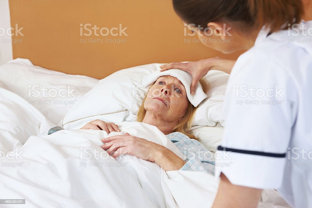 Nurse assisting senior woman suffering from fever stock photo